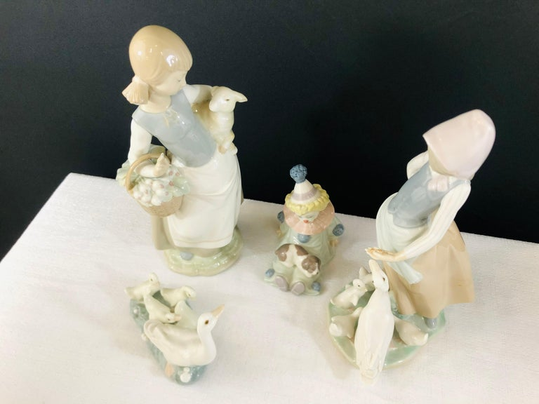 """A set of 4 Lladro (Spain) porcelain figurines. One figurine of a woman feeding ducks, one figurine of a woman holding a lamb, one of a group of ducks and the last one is a clown. Each figurine is signed in the bottom. Figurine 1: 5"""" L x 3.75"""" H x 2"""""""