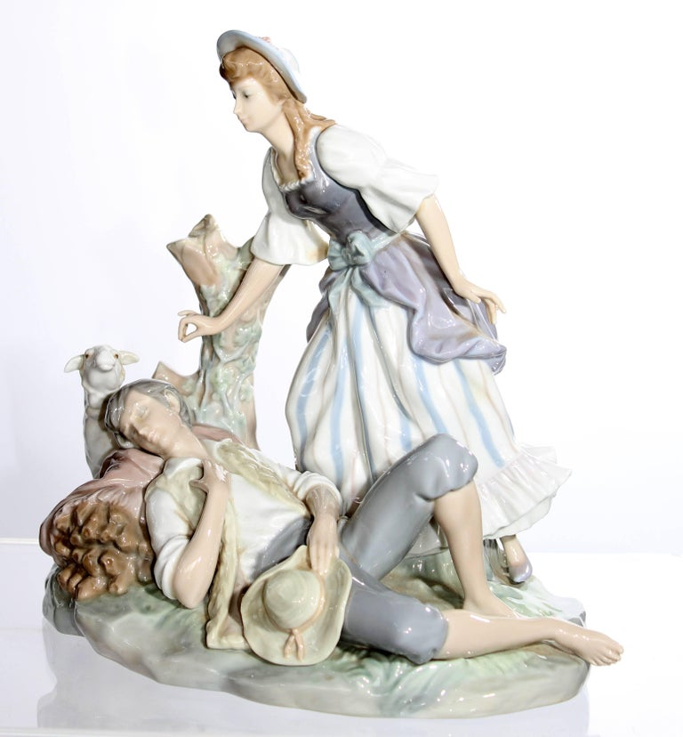 Lladro porcelain sculpture representing a woman leaning over a sleeping man with dog.