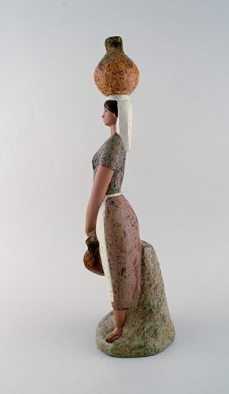Lladro, Spain. Large figure in glazed ceramics. Woman carrying water, late 20th century. Measures: 26.5 x 14.5 cm. In very good condition. Stamped.