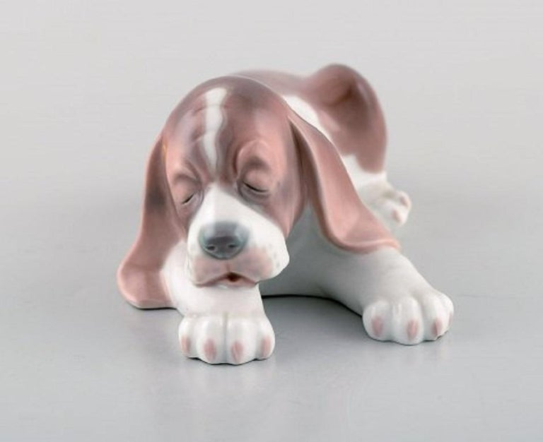 Lladro, Spain. Three porcelain figurines. Sleeping dog and two puppies, 20th century. In very good condition. Stamped. Largest measures: 18 x 5.5 cm.
