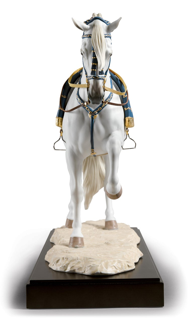 Limited edition sculpture of a Spanish horse trotting in position in matte porcelain, embellished with blue and gold lustre on the head, chest, saddle and blanket. Faithfully inspired by the examples at the Royal Andalusian School of Equestrian Art,