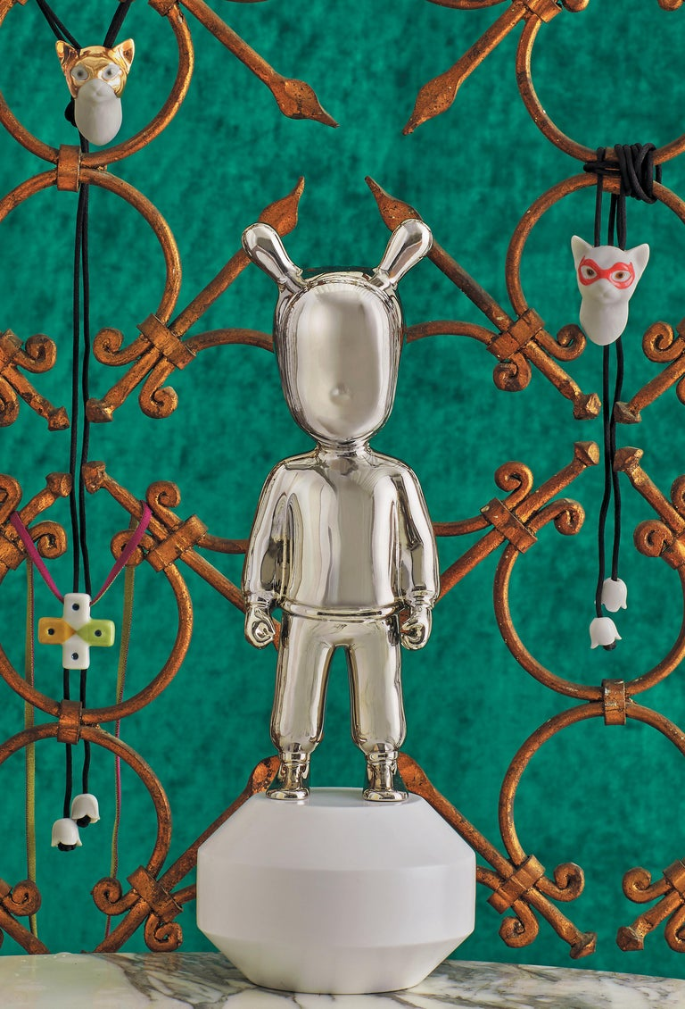Silver glossy porcelain figurine created by Jaime Hayon for The Guest by Lladró Atelier collection with a white base attached to the piece. The Guest is a piece created by Jaime Hayon for The Guest collection by Lladró Atelier, the brand's ideas