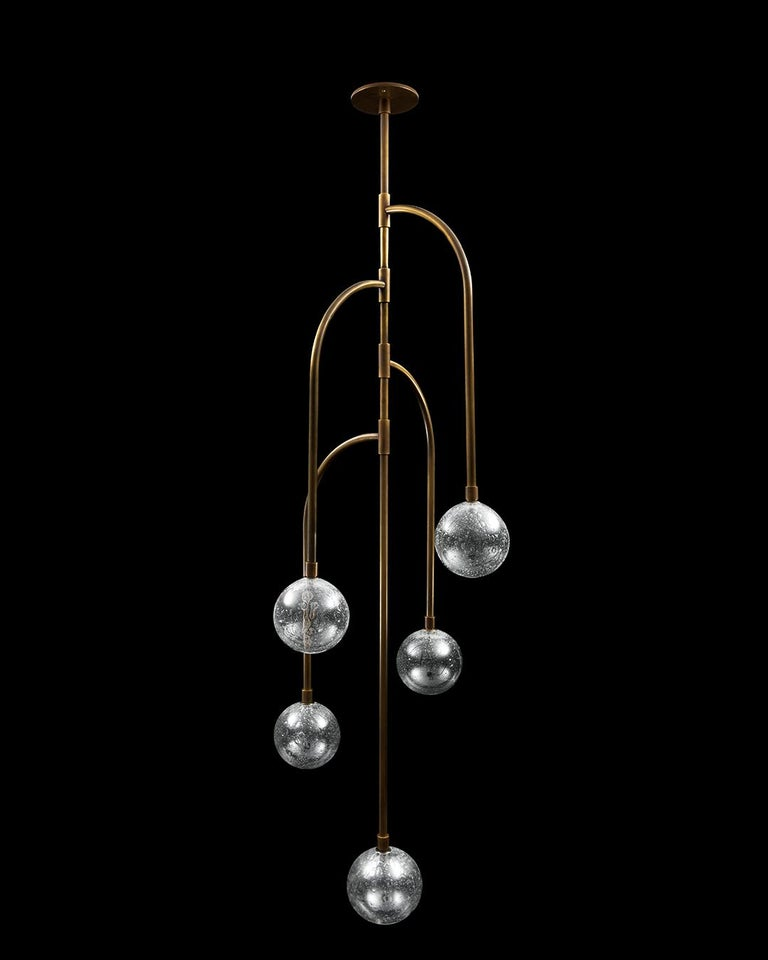 Inspired by the Latin American legend of the weeping mother, the Llorona lighting collection recalls the form of the weeping willow tree. The drooping brass branches rotate around a single axis, terminating in glass spheres of light.   Elegantly