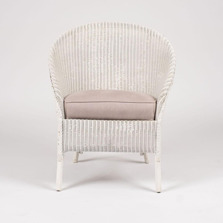 Lloyd Loom style white painted wicker chair. Sturdy, stabile condition with original steel spring seat. Upholstered in light color lavender linen.