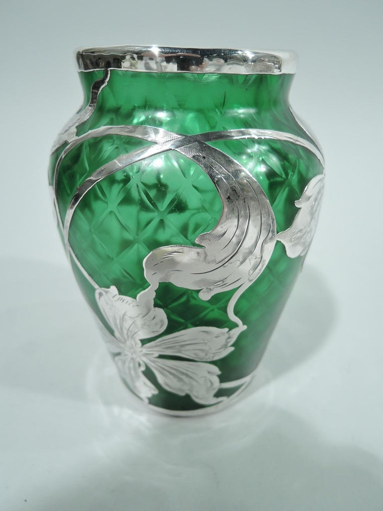 Turn-of-the-century Art Nouveau glass vase by historic Loetz with engraved silver overlay. Tapering sides, curved shoulder, and short straight neck. Overlay in form of loose, floaty flower heads and tendrils. Glass green and quilted. Pontil mark.