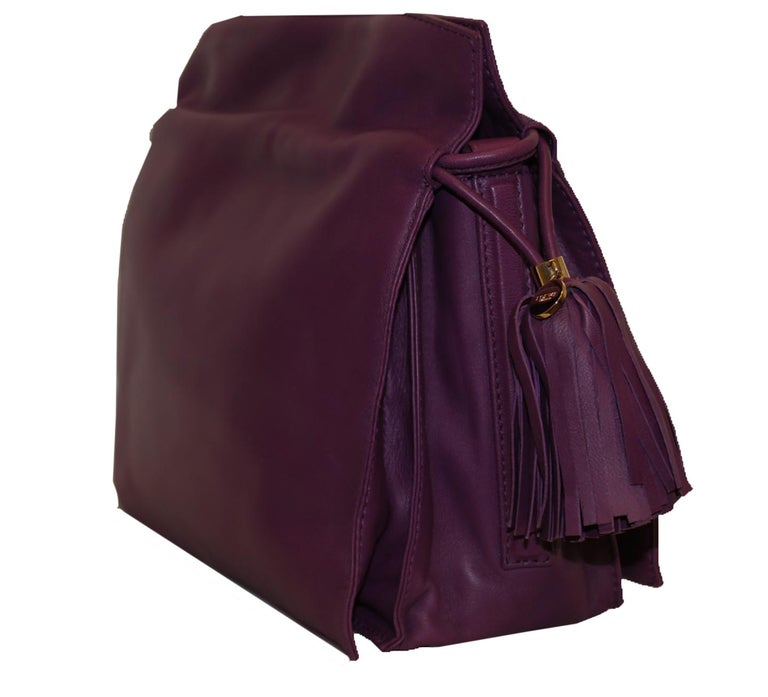 Loewe purple lambskin leather Flamenco bag with top handles incorporates a large tassel on each side with a drawstring for closure.  This bag opens to 3 compartments that are lined in beige linen and cotton.  One of the compartments includes a side