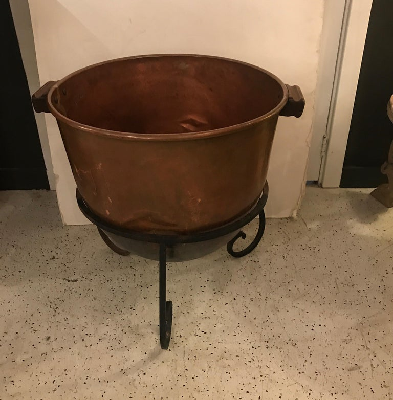 Unique copper log holder fashioned from a large copper candy making cauldron with wrought iron base. The pot showing the handmade dovetail seams. This early 20th century pot with wood handles was used for decades in the candy making process and with