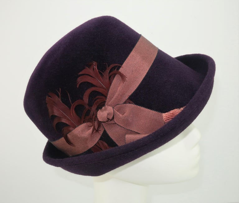 Modern meets old school with this updated wool trilby hat by New York milliner, Lola Ehrlich.  The deep aubergine or plum color is perfectly accented by a grosgrain ribbon and a fan of feathers. CONDITION The hat is in good previously owned