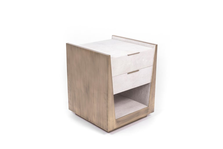 The Lola Bedside by R&Y Augousti is an elegant piece with its subtle geometry. This bedside table is completely inlaid in a mixture of cream shagreen and bronze-patina brass for a luxurious statement. The drawers are inlaid in gemelina wood, with