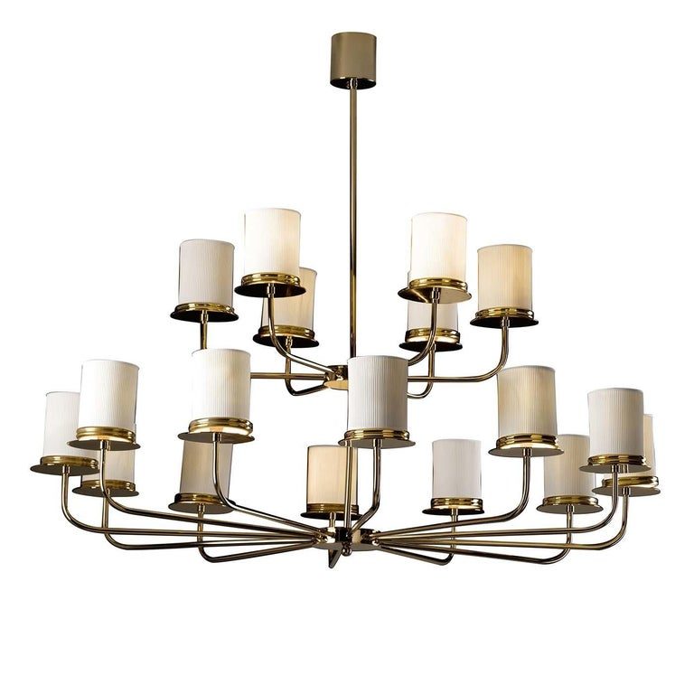 An imposing yet light structure distinguishes this stunning chandelier made of brass and arranged in two tiers with elegantly elongated arms supporting a total of 18 lightbulbs. Each light is delicately screened by a porcelain shade to provide a
