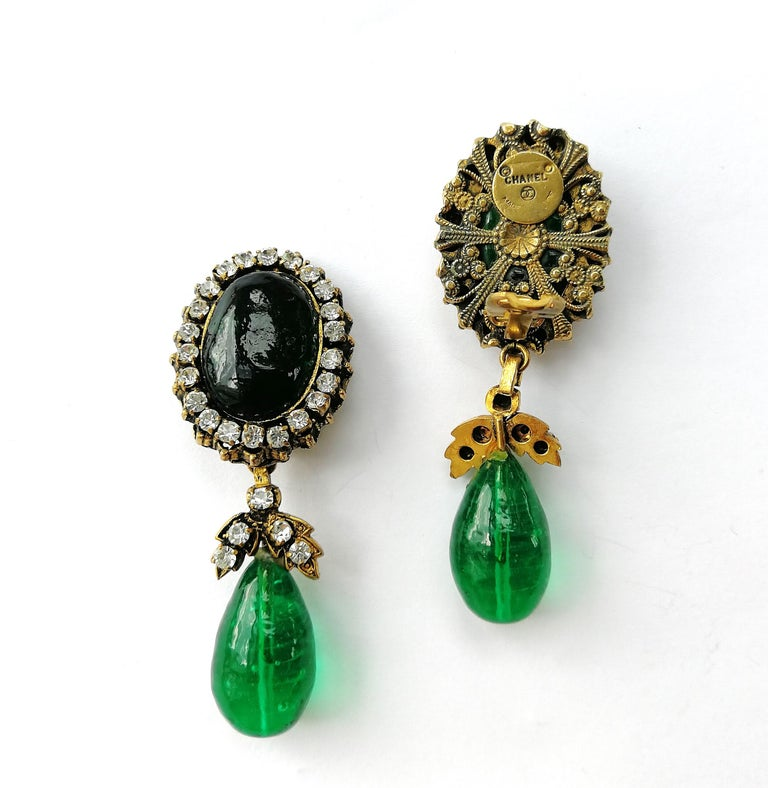 A beautiful and eye catching pair of emerald and clear paste drop earrings, made by Maison Gripoix for Chanel in the late 1970s/early 1980s. A large emerald poured glass cabuchon sits on the ear, circled in clear pastes, and a luscious emerald