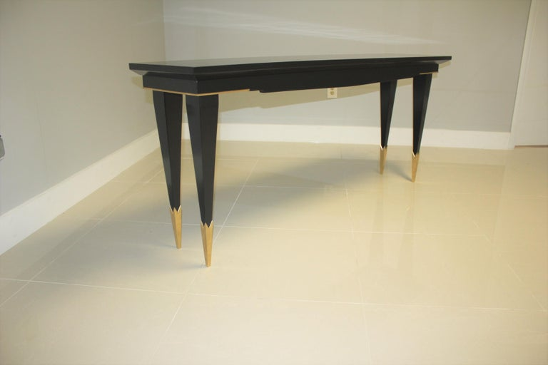 A beautiful long French Art Deco Style console table, circa 1940s. The mahogany wood has been ebonized and finished with a French polished high luster, the back of console table are finish too, the legs have brass toe caps, with beautiful brass