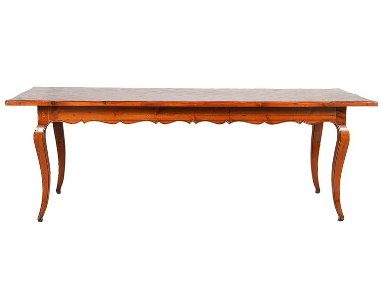 Of a glowing warm aged pine color this long French provincial style dining table features a beautiful pine parquetry top above a frame with carved scalloped apron resting on four carved cabriole legs.