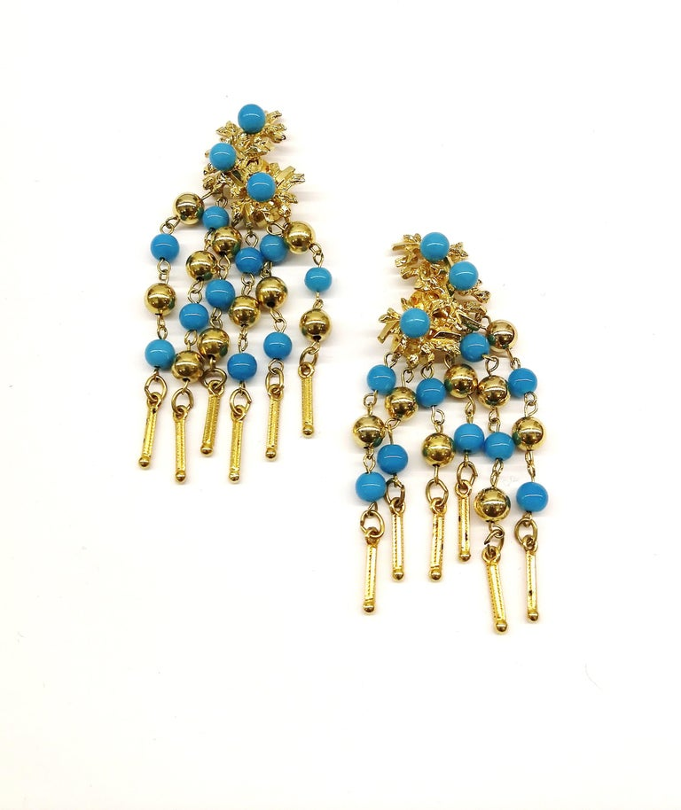 These fringed drop earrings from Christian Dior are a Summery and stylish addition to any wardrobe. With a design of abstracted gilt floral motifs on the top half of the earrings, set with round turquoise glass beads, the bottom half drops down in