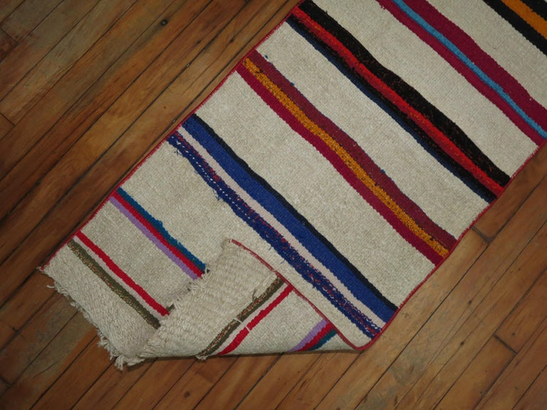 Colorful casual long Kilim runner from the mid-20th century. Bright pinks, black orange, lime green, fuchsia highlight the color accents on an ivory ground.