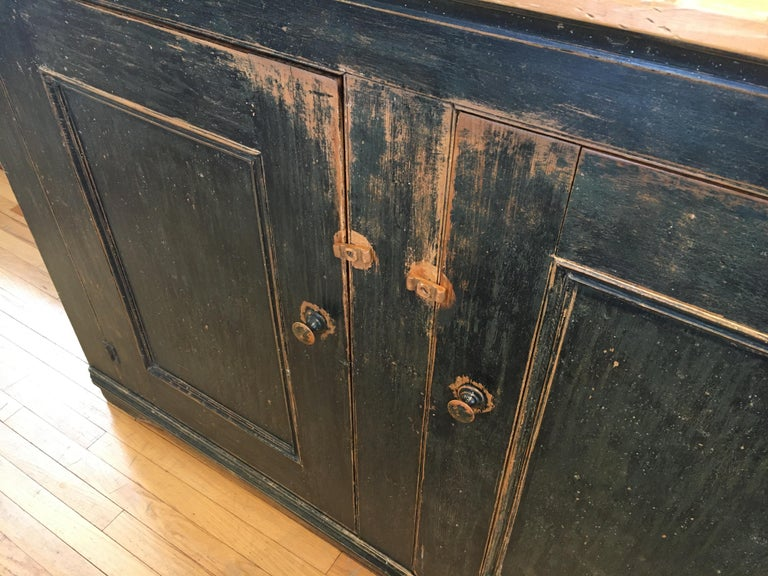 It is rare to find such a long two-door buffet that is also not too deep. This is not a massive piece but has enormous storage space with two inside shelves. The color is basically black, with tones of dark green and gray and a wonderful pine top.
