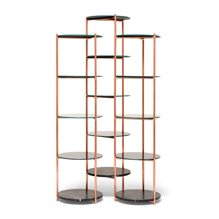 An essential but rich étagère, where each column rotates vertically and independently while remaining connected to the next, allowing the étagère to modify its foot-print and to hug curved walls and corners or to gather its 3 columns together to