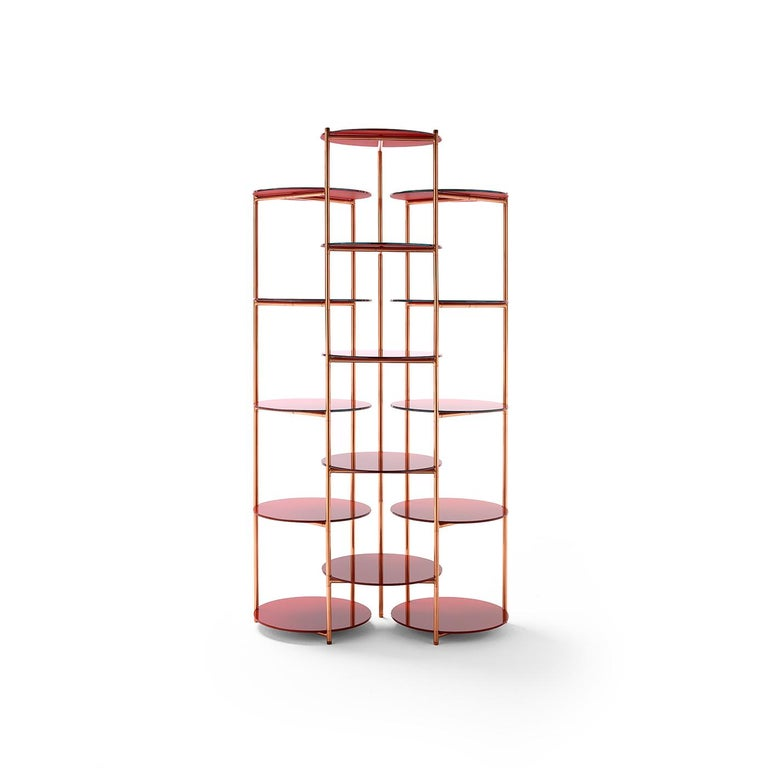 Built with a cylindrical frame combining steel and copper, this glamorous étagère has an open design. The three columns each feature five shelves in back-painted glass, creating a reflective, two-tone look that both pleases the eye and offers plenty
