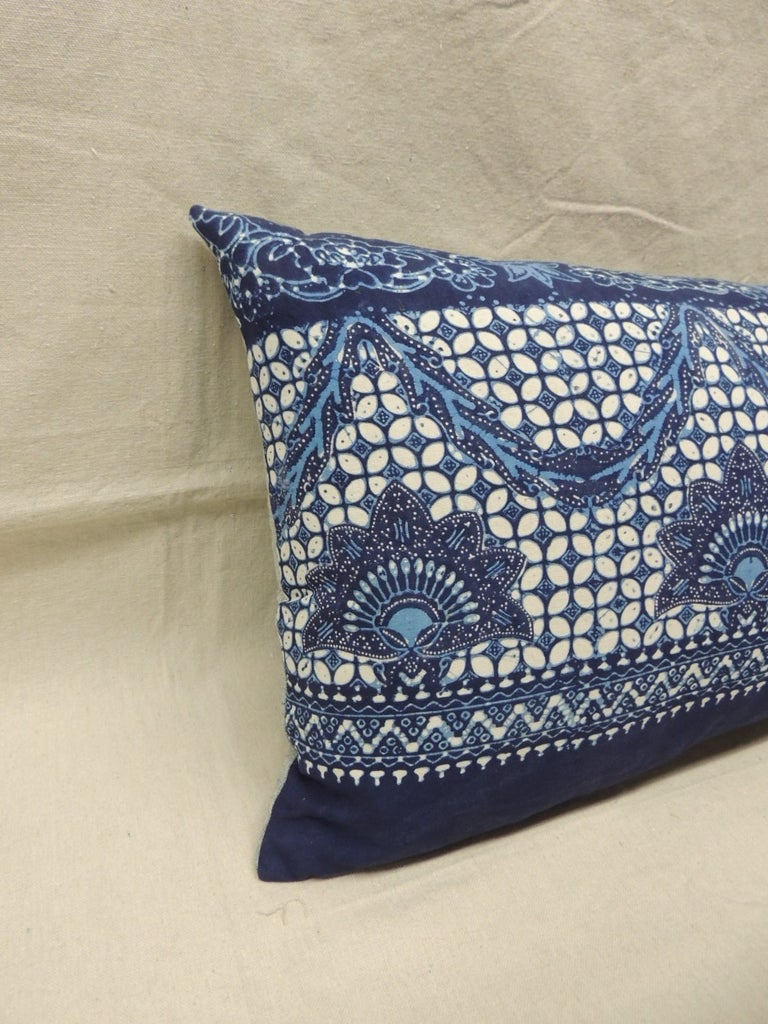 Large Indian blue and white hand-blocked batik bolster pillow on a deep blue background and blue strie´ linen backing.