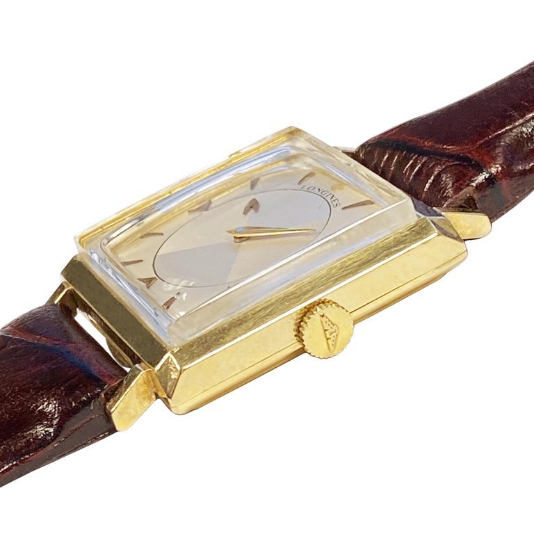 Circa 1950 Longines Mystery Dial Wrist Watch, 36 mm ( lug end to end ) X 37 mm. 14K yellow Gold 2 piece case, 17 jewel, mechanical, manual wind movement, original near mint condition 2 tone silver satin dial with raised Gold markers, center hour