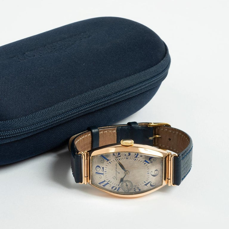Our extremely rare Longines manually wound 14k yellow gold dress watch with integral lugs and tonneau case features an unusual dial in silver with sub seconds and art deco cursive hand applied numerals dial in blue. This vintage Longines is