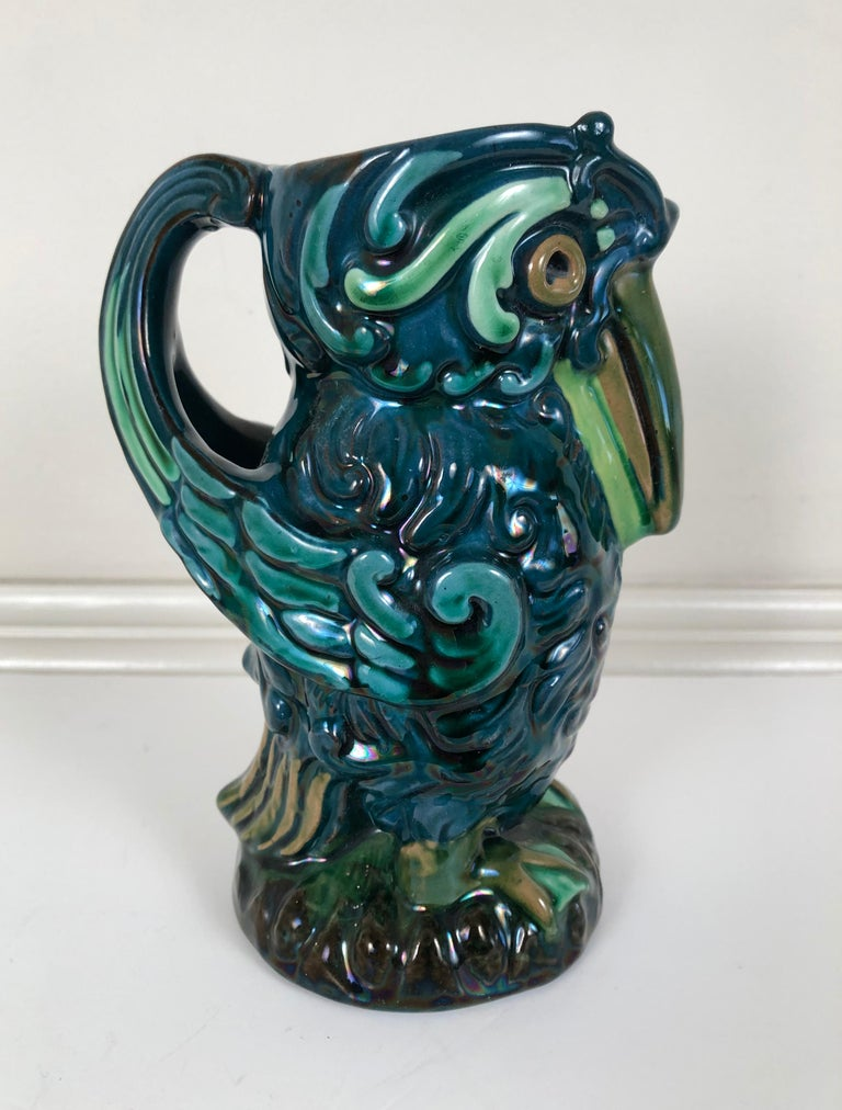 A Longpark English art pottery pitcher modeled as a bird in beautiful green, blue and brown glazes, with large eyes and beak and an integrated wing handle.