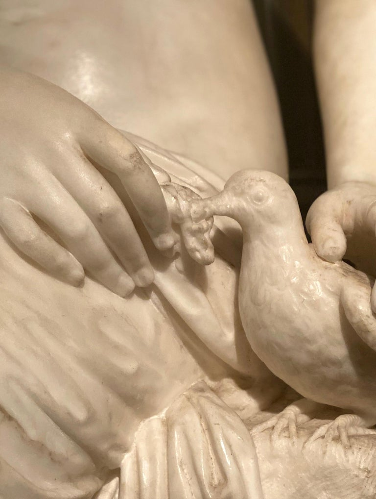 Delicious Neoclassical White Marble Sculpture of Seated Nymph feeding a dove .   The Neoclassical composition also incorporates drapery which is used to conceal her nudity.  The turn of the neck, but leans slightly forward, adding greater finesse to