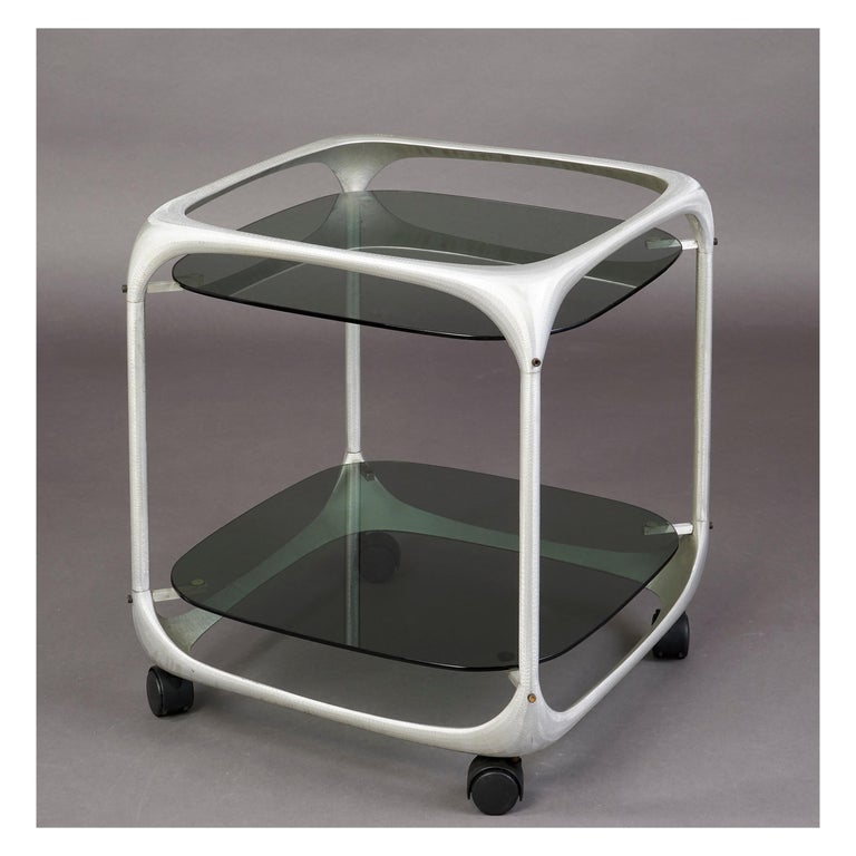 Lorenzo Burchiellaro( 1933-2017 ) Beautifully cubed two tiered rolling cart with rounded cast and textured aluminium form and smoked glass. A perfect 1960's Pop Art bar cart. Italy, 1960's Measures: 21 x 21 x 24 H.