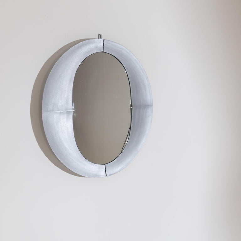 Round metal wall mirror with a ridged surface and oval mirror glass. Stamped Burchiellaro on the frame.