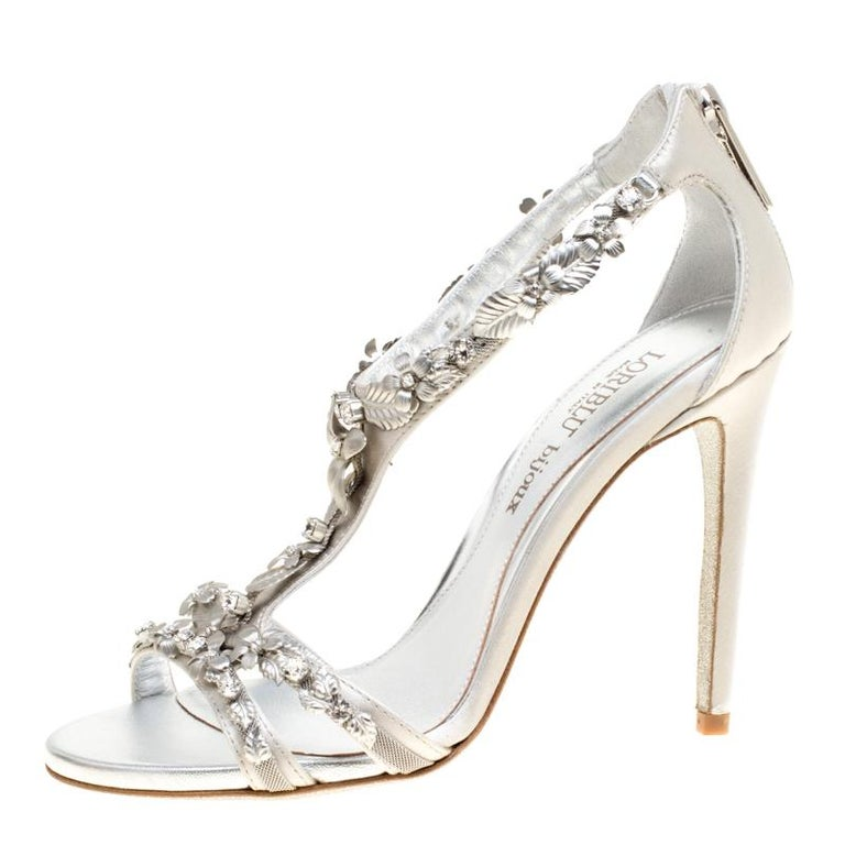 The intriguing silver-tone, floral embellishments that adorn the front straps and beautifully extend to the T-strap finishing just before the counters, make these grey satin sandals from Loriblu Bijoux a statement piece worth-possessing. The pair