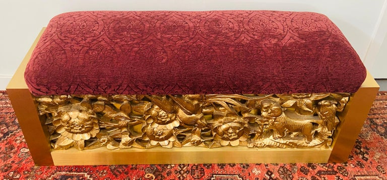 A stunning red suede top bench by Lorin Marsh. This one of a kind bench features a fine hand carved gilt wood base on both side (Front and Back). The bench sides are made of steel in an elegant beveled cut. The carving shows flowers, leafs, birds