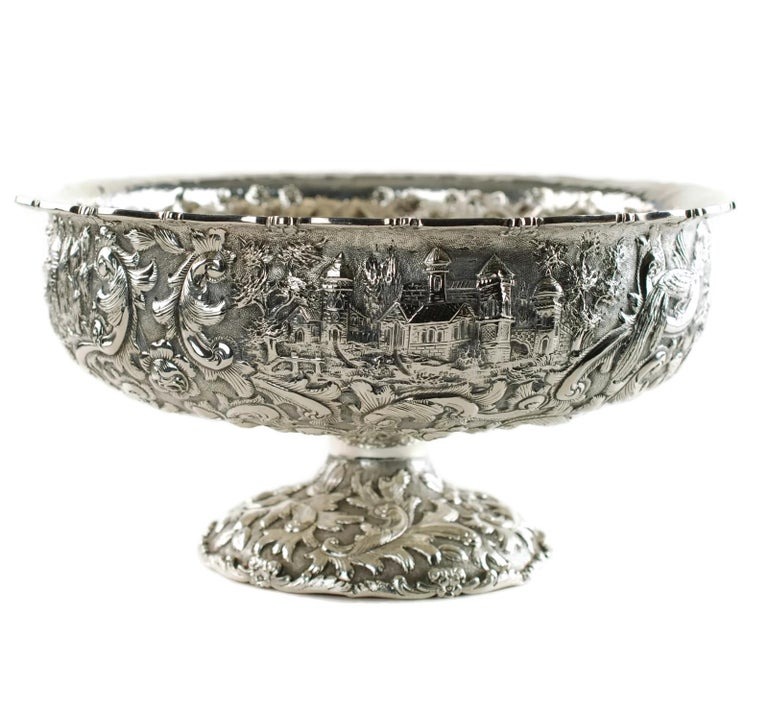 This large ornate early 20th century sterling silver centerpiece bowl has been made in the Castle pattern and is marked for The Loring Andrews Company of Cincinnati. The footed bowl features highly detailed all-over repoussé decoration which