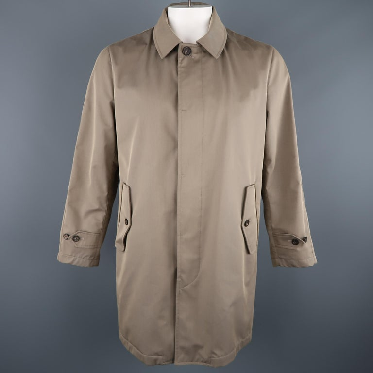 LORO PIANA Storm System rain coat comes in khaki cotton blend twill with a hidden placket button closure, flap pockets, tab cuffs, and detachable hood. Made in Italy.   New with Tags. Marked: L   Measurements:   Shoulder: 18 in. Chest: 46