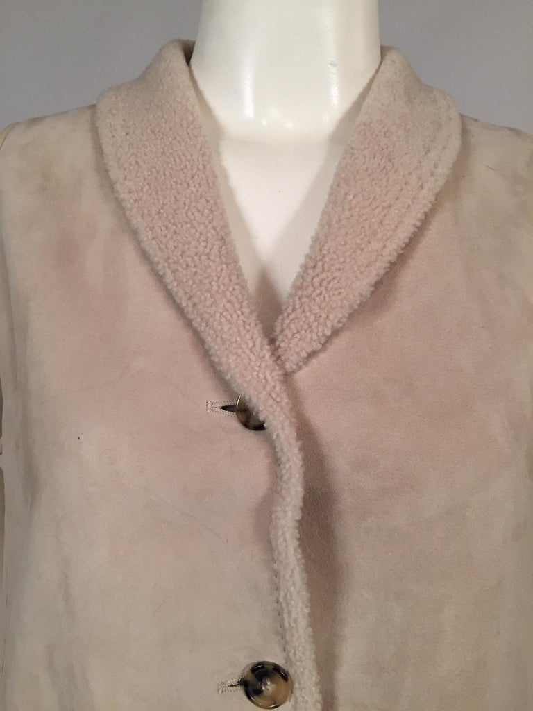 A light weight shearling vest is perfect for layering now and wearing alone when the temperatures begin to warm up. It has a shawl collar, four logo buttons, and there are pockets in the side seams. It is in excellent condition and appears to have