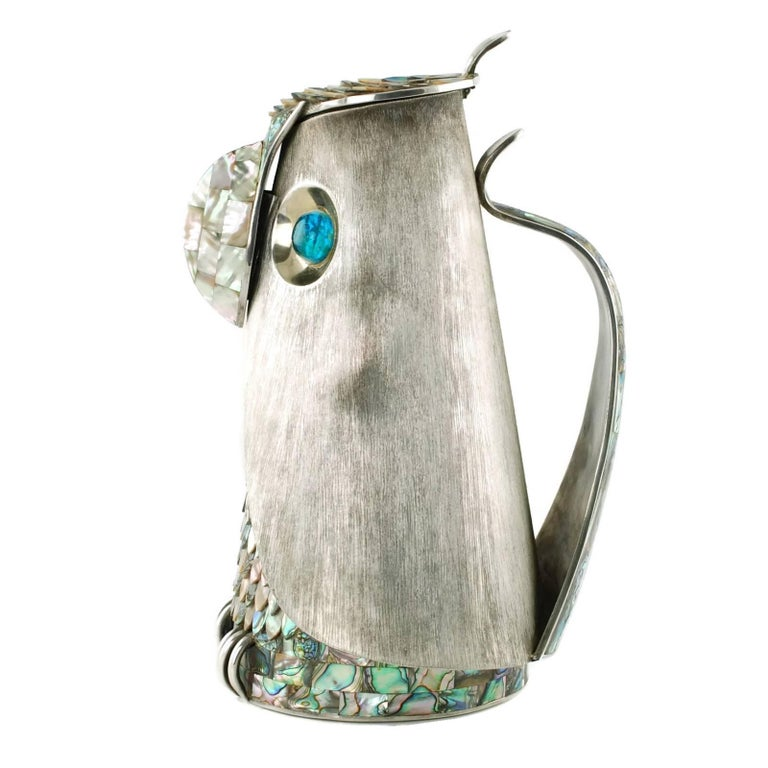 This MCM lidded pitcher was made by highly regarded taller Los Castillo of Mexico. The piece has been made in the form of a stylized owl and features a brushed silver plate exterior along with abalone accents in the form of overlapping feather