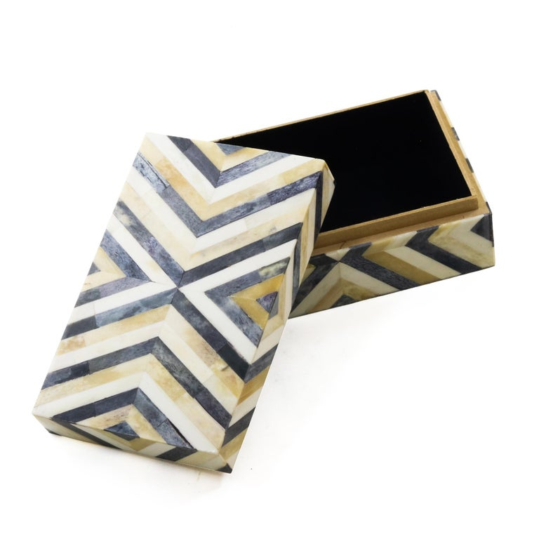 An ivory and brown decorative bone box. Features an all over playful triangular pattern.