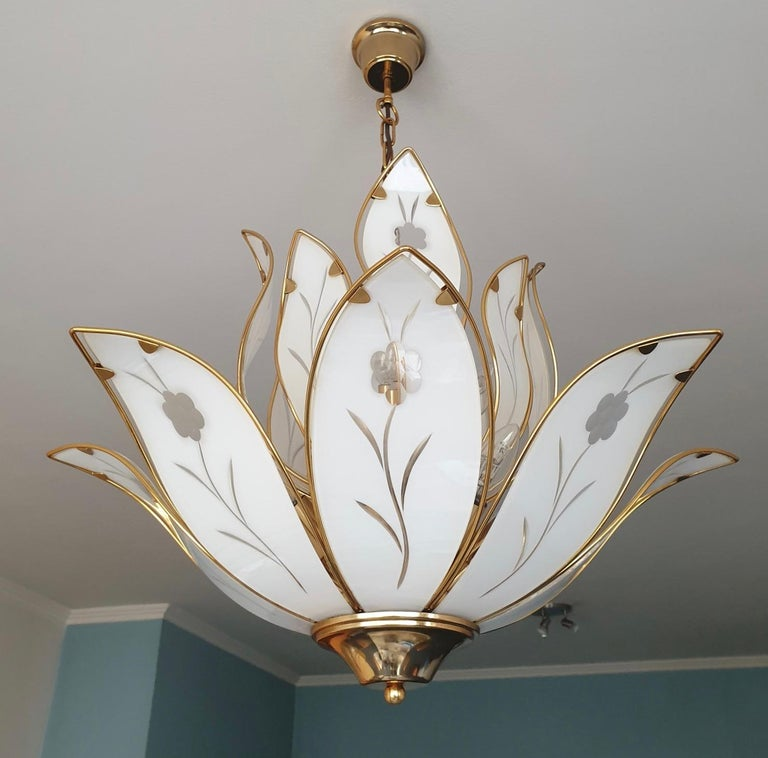 Elegant brass Lotus chandelier with white Murano glass leaves. Measures: Diameter 67 cm. Height fixture 48 cm. Total height including the chain and canopy 85 cm. Twelve E14 bulbs.
