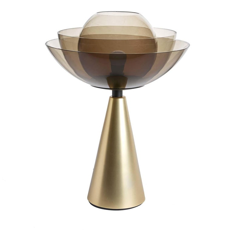 A fascinating design inspired by the lotus flower, this stunning table lamp embodies elegance, perfection, purity, and grace. Designed by Serena Confalonieri, this lamp is composed of a cone-shaped base in brass-coated iron with a stunning shade