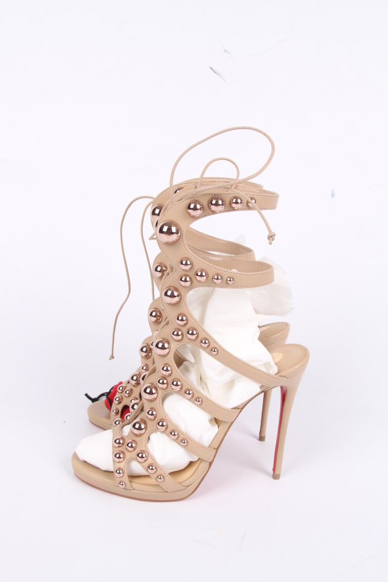 Fantastic pair of sandalettes by Christian Dior with the wonderful name Amazoubille.  Crafted from nude/beige leather embellished with rose gold-tone studs in different sizes. Lace-up closure at the front. A straight heel that measures as much as 12