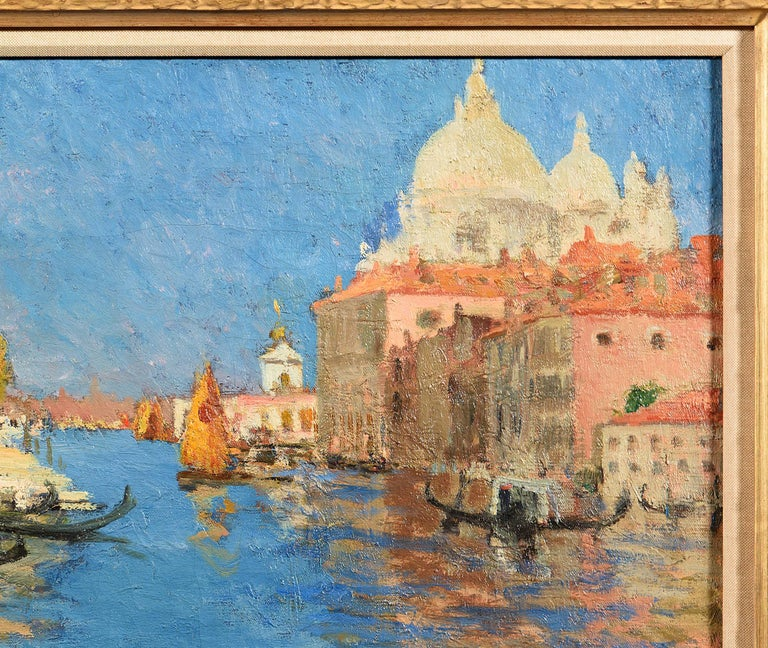 Unframed dimensions specified.  Signed (lower left)  This is a vibrant painting of Venice's Grand Canal, with the ebullient hues of orange, salmon, and mustard typical to Mediterranean architecture and the vivid blue sky bouncing off the
