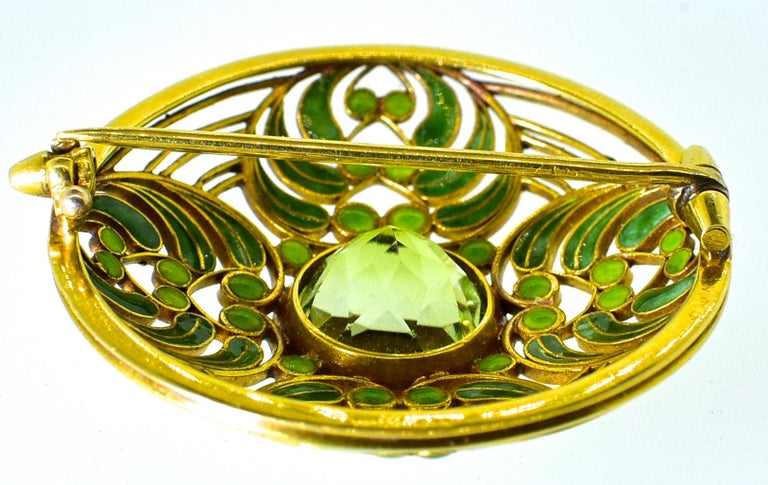 L.ouis Comfort Tiffany antique gold brooch decorated with plique a jour green enamel - and centering a round tourmaline weighing over 5 cts.  This 18K brooch is large and robust, signed Tiffany & Co., and is unquestionably a masterpiece by Louis
