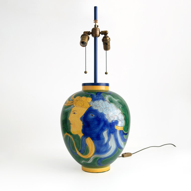 Large, Louis Drimmer ceramic table lamp with a blue and yellow face on a green glazed ground. Newly wired with patinated brass, standard base double cluster sockets. Stem, finial and mounting are custom brass stained in blue, Made in France, 1970.
