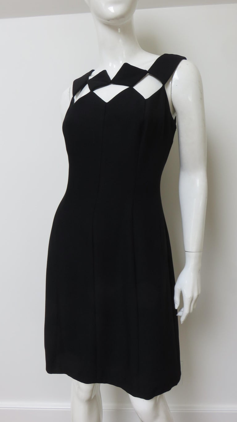 A fabulous little black dress from Louis Estevez.  It is sleeveless with the front and back neckline comprised of squares of fabric leaving squares of exposed skin.  The dress is a subtle A line fully lined with a back hand sewn zipper. Fits sizes