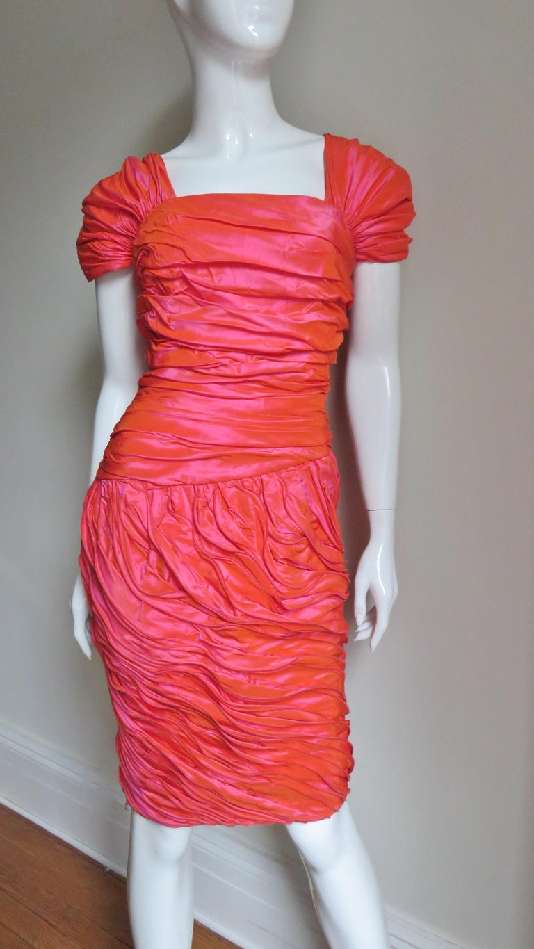 A gorgeous coral silk dress from Louis Feraud.  In the light the silk is several shades of coral and rose coral.  The dress has gathered cap sleeves over the shoulders and ruching across the bodice from front and back to the drop waist.  The tulip