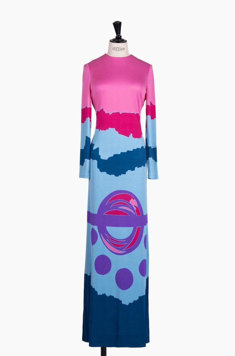 This eye-catching c. 1970 Louis Féraud maxi dress shows a clashing abstract mod pattern in various shades of pink, blue and purple. It features a figure-hugging silhouette, a round neck, bust darts and long sleeves. The dress is made from a