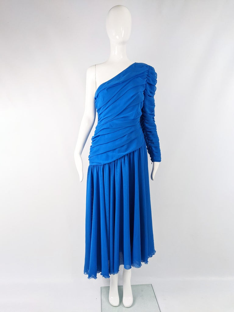 A beautiful vintage evening dress from the 80s by Parisian fashion designer, Louis Feraud. In a blue ruched chiffon with one sleeve, an asymmetrical cut and a gathered skirt.  Size: Marked vintage 42 but fits like a modern womens UK 10/ US 6/ EU 38.