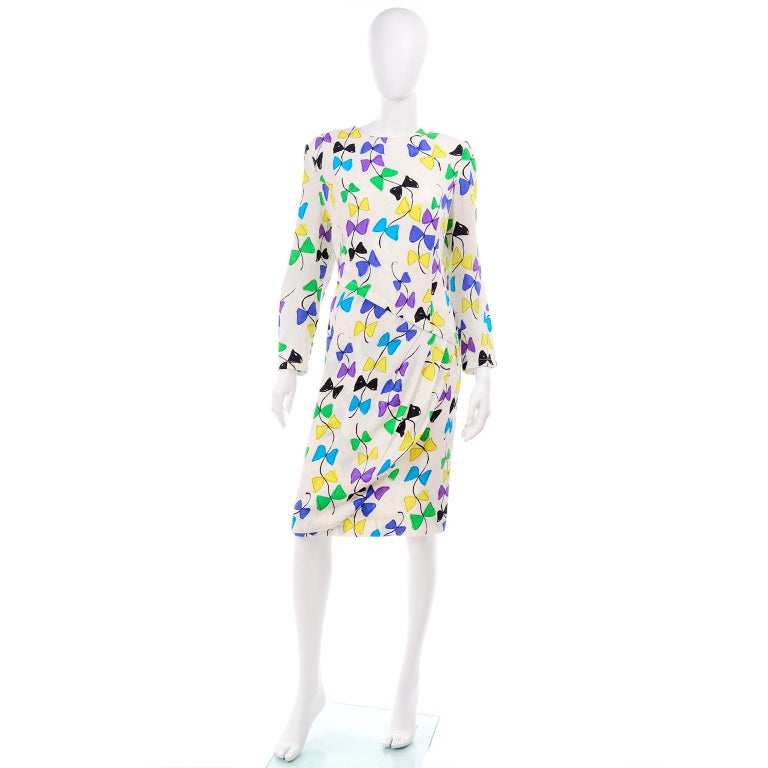 Vintage Louis Feraud dress in a colorful novelty print. This lovely vintage dress is lined and has a round neck and a pleated faux wrap detail at the asymmetrical waist.  We love novelty prints and this one is so pretty, with shades of blue, green,