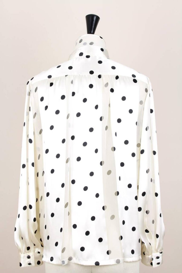 This is a wonderful semi-transparent polka dot silk blouse by Louis Féraud from the 1980s. It is made from alternating high quality silk satin and silk chiffon in a cream hue with black polka dots. The blouse features a high neck with a tie that is