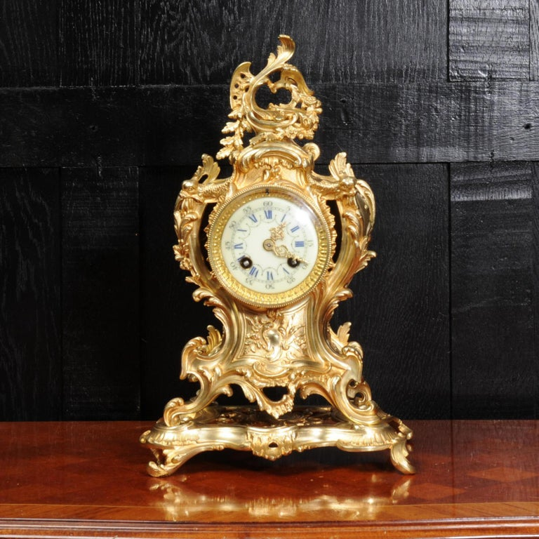 A lovely antique French clock by Louis Japy and retailed by Maison Henri Riondet of Paris. It is beautifully modelled in gilded bronze, waisted Rococo shape mounted on an integral base. Profusely decorated with dolphins to the shoulders, 'C' scrolls