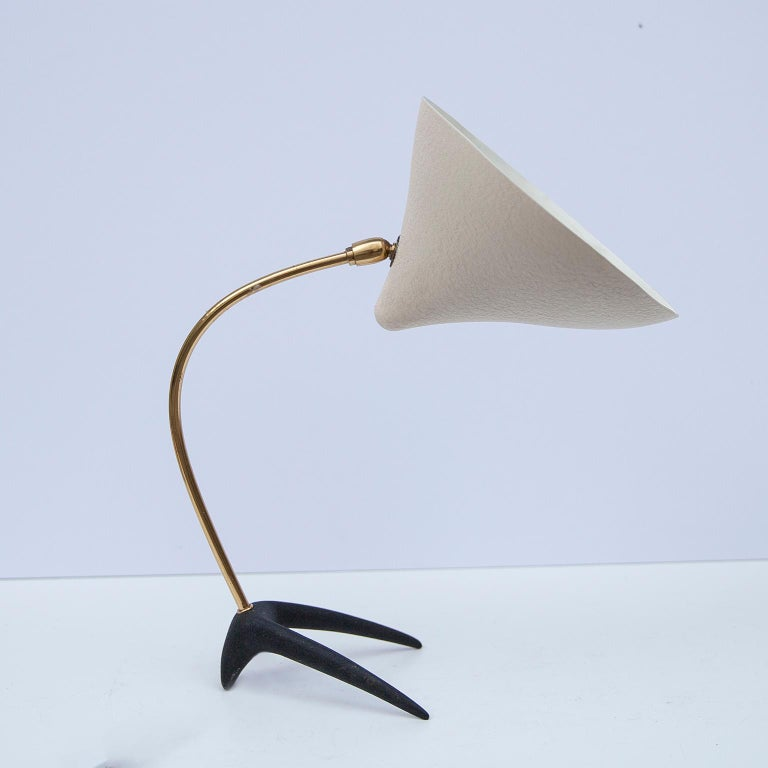 Vintage table lamp with a cast iron foot and a curved brass base, designed by Louis Kalff in the 1950s for Philips Netherland. The conical shade was made of aluminium, white lacquered. The table lamp has an on/off switch and an original E 27